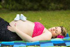 Pregnant woman lying in green grass Royalty Free Stock Image