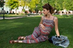 Pregnant woman lying on green grass outdoors. Motherhood. Stock Photography