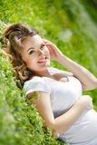 Pregnant woman lying on green grass in the park Stock Images