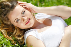 Pregnant woman lying on green grass in the park Stock Photos