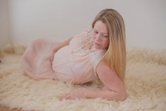 Pregnant woman lying on rug Royalty Free Stock Images