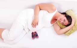 Pregnant woman lying on the sofa in front of baby boots. Royalty Free Stock Photo