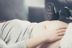 Pregnant woman lying on the sofa and holding shoes unborn child. Royalty Free Stock Image