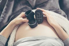 Pregnant woman lying on the sofa and holding shoes unborn child. Stock Images