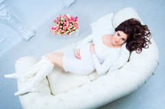 Pregnant woman lying on a sofa near a basket with tulips Royalty Free Stock Photo