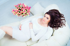 Pregnant woman lying on a sofa near a basket with tulips Royalty Free Stock Photography