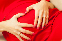 Pregnant woman makes heart shape over belly Stock Photo