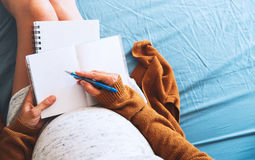 Pregnant woman makes notes and looking at medical documents. Royalty Free Stock Image
