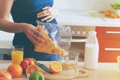 pregnant woman making breakfast with corn flakes Stock Images