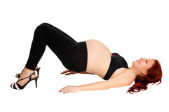 Pregnant woman making bridge. Royalty Free Stock Photos