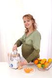 Pregnant woman making fresh fruit juice Royalty Free Stock Image