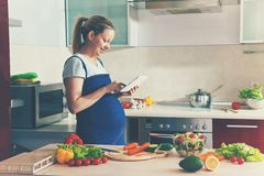 Pregnant woman making salad with digital tablet Stock Photography