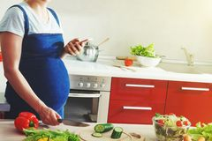 Pregnant woman making salad with smart phone Stock Images