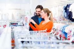 Pregnant woman and man buying baby clothes Stock Photography