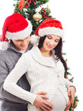A pregnant woman and a man celebrating Christmas. A young and pregnant women and a happy men celebrating Christmas. The image is taken near the Christmas tree Royalty Free Stock Photo