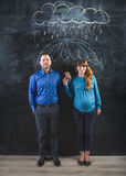 Pregnant woman and man covering under umbrella drawn on blackboa Stock Photography