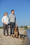 Pregnant woman and man with dog Royalty Free Stock Image