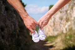 Pregnant woman and man holding baby shoes in hands. Future mom and dad, parents is holding little newborn baby shoes. Stock Image