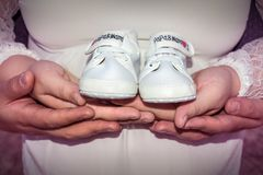 Pregnant woman and man holding baby shoes royalty free stock photography