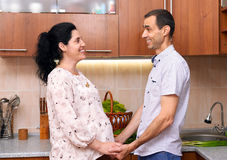 Pregnant woman and man in kitchen interior with fresh fruits and vegetables, healthy food concept, happy couple royalty free stock image