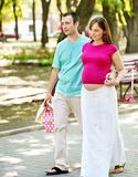 Pregnant woman with man outdoor. Pregnant couple holding shopping bag outdoor stock image