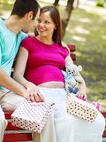 Pregnant woman with man outdoor. Pregnant woman, holding shopping bag with men outdoor stock images