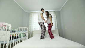 A pregnant woman and a man in pajamas dancing on the bed. stock video