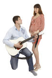 Pregnant woman and a man playing guitar for her Stock Photography