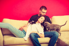 Pregnant woman and man relaxing on sofa Royalty Free Stock Image