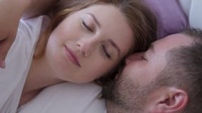 Pregnant woman and a man in white t-shirts lying stock footage