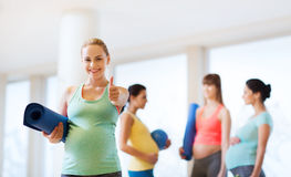 Pregnant woman with mat in gym showing thumbs up Stock Photos