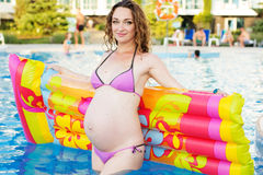 Pregnant woman with mattress near swimmimg pool Stock Photos