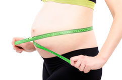 Pregnant woman measures the abdominal circumference centimeter tape, closeup Royalty Free Stock Photo