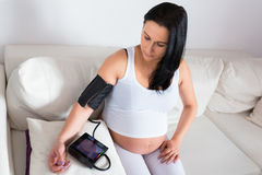 Pregnant woman measures the blood pressure. On the sofa Royalty Free Stock Photo