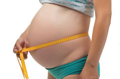 Pregnant woman measures her belly. Stock Photos