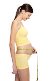Pregnant woman measures her stomach Royalty Free Stock Photo