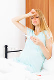 Pregnant woman measures the temperature with thermometer Royalty Free Stock Image