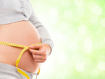 A pregnant woman measuring her belly with a tape Stock Photo