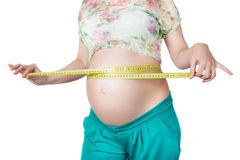 Pregnant woman measuring her waist and stomach. Royalty Free Stock Images
