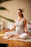 Pregnant woman meditates indoor in yoga pose. Stock Image