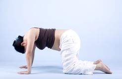 Pregnant Woman Meditating. Isolated pregnant woman exercising yoga over blue background Royalty Free Stock Images