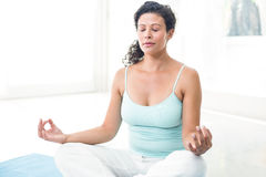 Pregnant woman meditating in lotus position Stock Photo