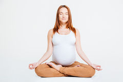 Pregnant woman meditating in lotus position Stock Image