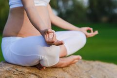 Pregnant woman in meditation pose on stone. Grass in the park. Close-up of crossed legs of female with hand on her knee. Green lawn and sky in the background Stock Image