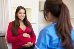 Pregnant Woman Meeting With Nurse In Clinic Stock Photo