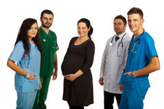 Pregnant woman in the middle on doctors Royalty Free Stock Images