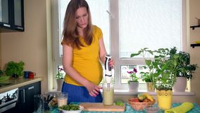 Pregnant woman mix milk and natural fruits cocktail with blender tool in kitchen. Pregnant woman mixing milk and natural fruits cocktail with blender tool in stock footage