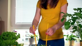 Pregnant woman mixing salad in glass dish stock footage