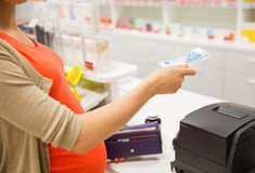 Pregnant woman with money at cashbox in drugstore Stock Photography