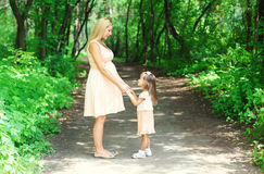 Pregnant woman, mother and little child walking together in summer stock photos